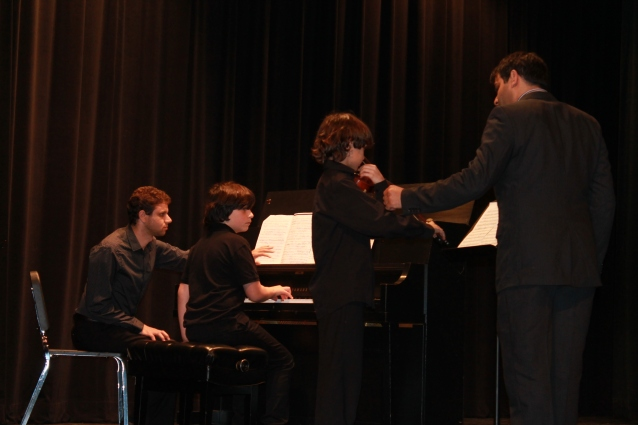 Polyphony Co-Founder Nabeel Abbhoud Ashkar assists Nasif Francis, 10, on the violin as pianist Ron Trachtman assists David Margalit, 12, on the piano.