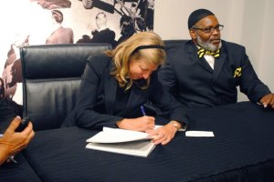 "Dorothy Budd and Billy Smith sign copies of their book ""Tested"""